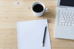 白纸、铅笔、膝上型计算机和咖啡在木桌上 库存照片