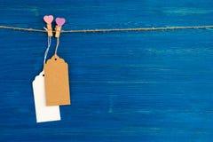 白纸价牌或在心脏和木别针装饰的标号组垂悬在蓝色木背景的一条绳索 库存照片