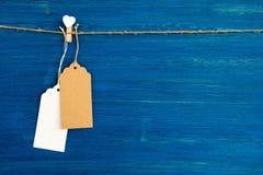 白纸价牌或在白色心脏和木别针装饰的标号组垂悬在蓝色木背景的一条绳索 免版税库存照片