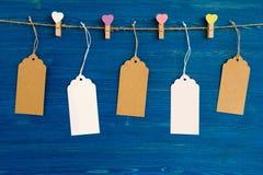 白纸价牌或在色的心脏和木别针装饰的标号组垂悬在蓝色木背景的一条绳索 免版税库存照片