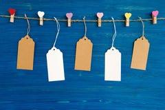 白纸价牌或在色的心脏和木别针装饰的标号组垂悬在蓝色木背景的一条绳索 库存照片