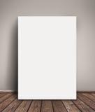 白纸倾斜对墙壁的海报嘲笑 免版税库存照片