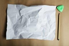 白纸和一支铅笔板料在棕色背景 免版税库存图片