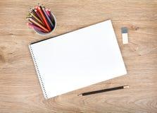 白纸和五颜六色的铅笔在木桌上 免版税库存照片