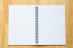 白纸在木桌背景的笔记本 免版税库存图片