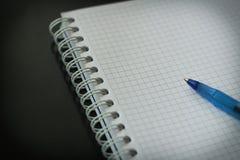 白纸摆正了文本的笔记本与在黑背景关闭的蓝色笔 免版税库存图片