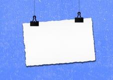 白纸框架由在蓝色难看的东西墙壁背景的夹子垂悬了 免版税库存照片