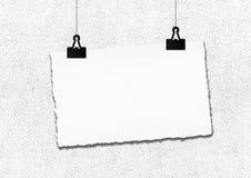 白纸框架由在难看的东西墙壁背景的夹子垂悬了 库存图片