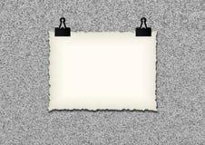 白纸框架由在难看的东西墙壁背景的夹子垂悬了 免版税库存照片