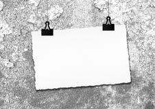 白纸框架由在难看的东西墙壁背景的夹子垂悬了 免版税库存图片