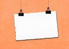 白纸框架由在难看的东西墙壁背景的夹子垂悬了 图库摄影