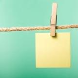 白纸注意垂悬在与晒衣夹的绳索,拷贝空间 免版税库存照片