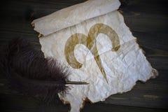 白羊星座黄道十二宫在葡萄酒纸的与在木书桌上的老笔 免版税图库摄影