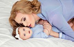 白肤金发一个美丽的妈妈和有b的一个小女孩婴孩的画象 库存图片
