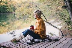 白肤金发与坐在有杯子的湖附近的蓝眼睛热的茶 库存照片