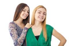 白肤金发两个微笑的可爱的十几岁的女孩-和浅黑肤色的男人摆在 免版税库存照片