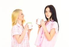 白肤金发和深色在微笑的面孔拿着杯子用咖啡 喝茶或咖啡的女孩在早晨,隔绝在白色 库存图片