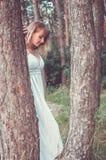 白肤金发在杉木之间的白色礼服立场 免版税库存图片