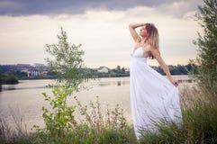 白肤金发在白色礼服在河附近 图库摄影