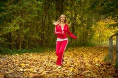 白肤金发女孩少妇跑的跑步在秋天秋天森林公园 免版税库存图片