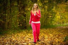 白肤金发女孩少妇跑的跑步在秋天秋天森林公园 免版税库存照片