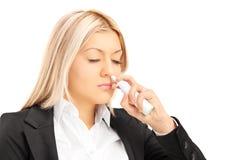 年轻白肤金发女性喷洒在她的鼻子下降 免版税图库摄影