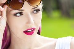 白肤金发妇女的太阳镜和洋红色桃红色头发 库存图片