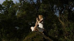 白肤金发少妇思考室外在莲花瑜伽位置在森林- 股票录像