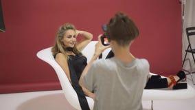 白肤金发式样在妇女摄影师被拍摄的扶手椅子 股票录像