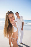 白肤金发微笑对与握她的手的男朋友的照相机 免版税库存图片