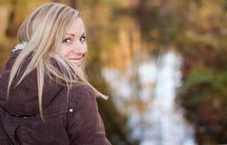 白肤金发愉快查找在肩膀的她 免版税图库摄影