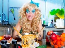 白肤金发滑稽在有饥饿的意大利面食的厨房 库存图片