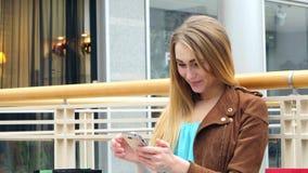 白肤金发的与电话的妇女坐的购物中心 股票录像
