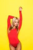 年轻白肤金发的亭亭玉立的红色身体的妇女体操舞蹈家在黄色背景 库存照片