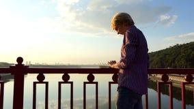 白肤金发的人在河桥梁站立并且投入他的想法下来在日落 股票录像