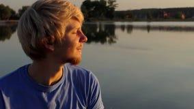 白肤金发的人在slo mo喝咖啡坐湖银行在日落 影视素材