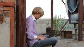 白肤金发的人坐建筑地方并且工作在他的膝上型计算机 股票视频
