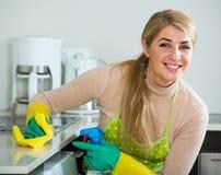白肤金发的佣人清洁在厨房里 免版税库存图片