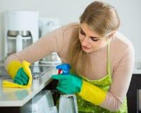 白肤金发的佣人清洁在国内厨房里 免版税库存图片