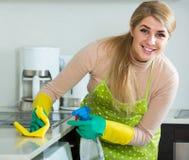 白肤金发的佣人清洁在国内厨房里 免版税图库摄影