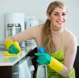 白肤金发的佣人清洁在国内厨房里 免版税库存照片