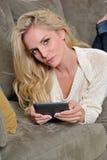 白肤金发的使用妇女的计算机e阅读程& 图库摄影