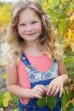 白肤金发的俏丽的儿童女孩在葡萄庭院里 图库摄影