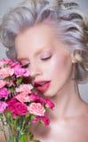 白肤金发的俏丽的妇女秀丽画象有花的 免版税库存照片