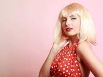 白肤金发的假发减速火箭的红色礼服的画报女孩。葡萄酒。 免版税库存图片