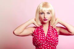 白肤金发的假发减速火箭的红色礼服的画报女孩。葡萄酒。 免版税库存照片