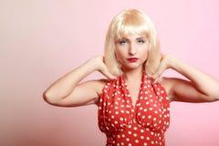 白肤金发的假发减速火箭的红色礼服的画象美丽的画报女孩。葡萄酒。 库存照片