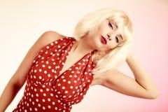 白肤金发的假发和减速火箭的礼服的画报女孩 葡萄酒 免版税图库摄影
