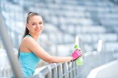 年轻白肤金发的健身妇女开会,水合和为跑做准备 Sprint,跑步和台阶锻炼在室外一个的晴天 库存图片