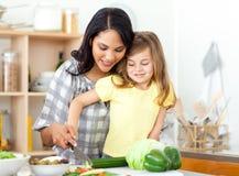 白肤金发的儿童剪切她的母亲蔬菜 免版税库存图片